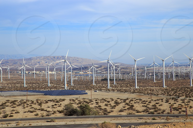 long exposure photography of wind turbines in brown field under blue sky during daytime photo