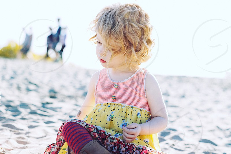 girl in white and yellow tank dress sitting on gray sandy beach during daytime photo