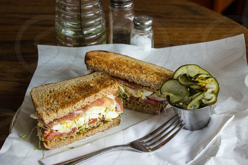 sandwich with bacon and mayonnaise dressing beside stainless steel form near pickles photo