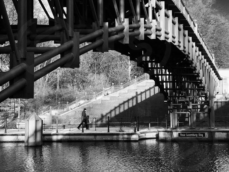 Berlin Germany Europe walking man bridge under below park outdoor river canal riverside river bank street black and white photo