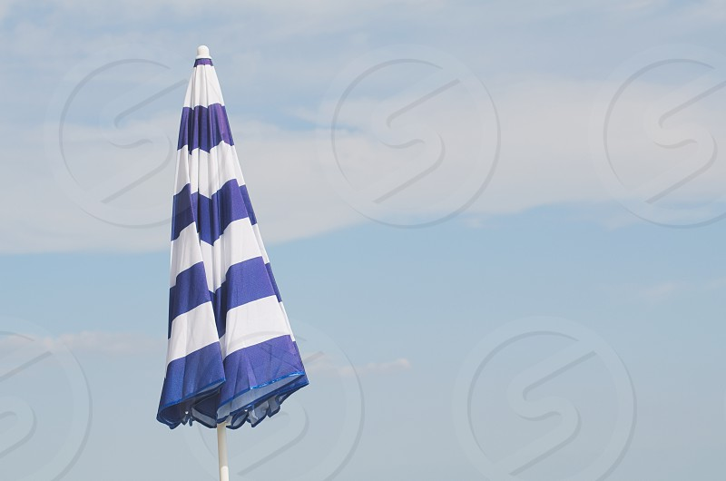 Blue and White Striped Closed Parasol against Summer Blue Sky photo