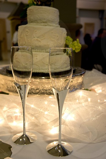 Champagne toasting flutes and wedding cake photo