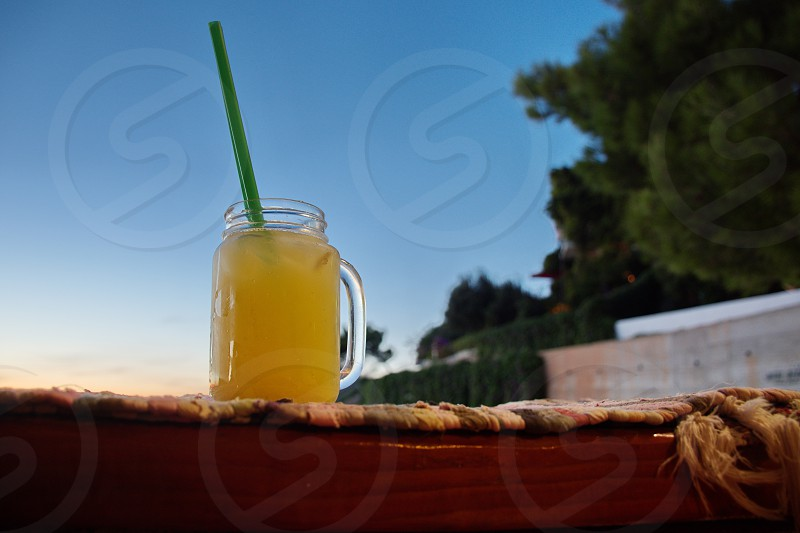Closeup of orange juice in the drinking glass witj straw on the wooden fence photo