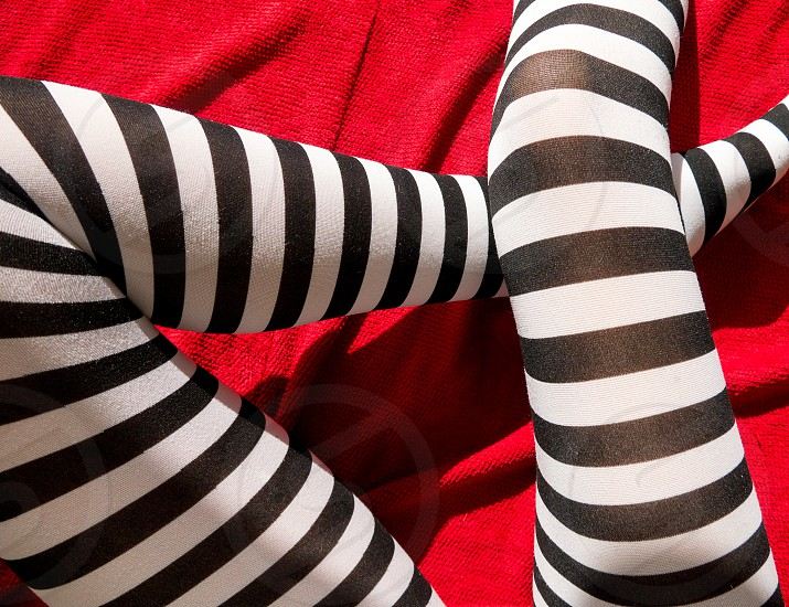 Candystripe legs. Colour close up of a woman's bent legs in black and white striped tights against a red textured background photo