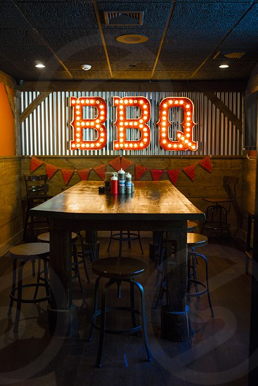 brown wooden rectangular dining table surrounded by brown wooden round stool  inside bbq store photo
