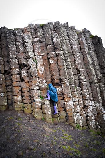 Climbing the rocks of the Giants Causeway in rainy northern Ireland photo