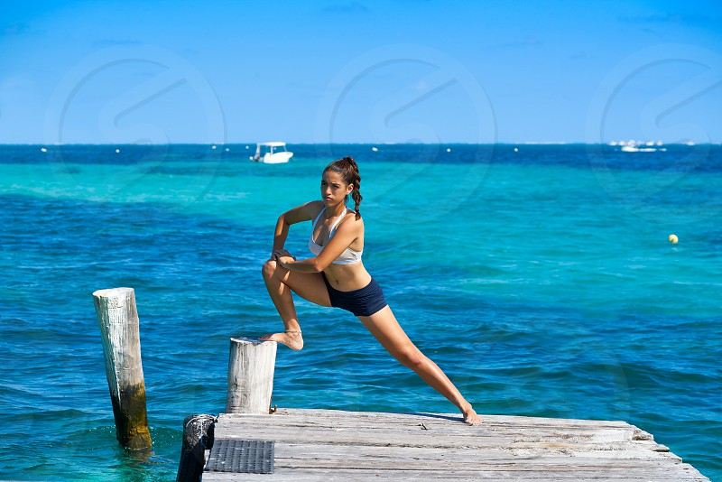 Latin athlete woman stretching in Caribbean beach pier photo