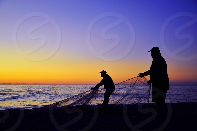 view of fisherman catching fish through fish nets photo