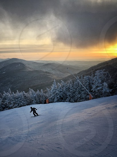 golden hour time in man riding ski blades on snow field photo