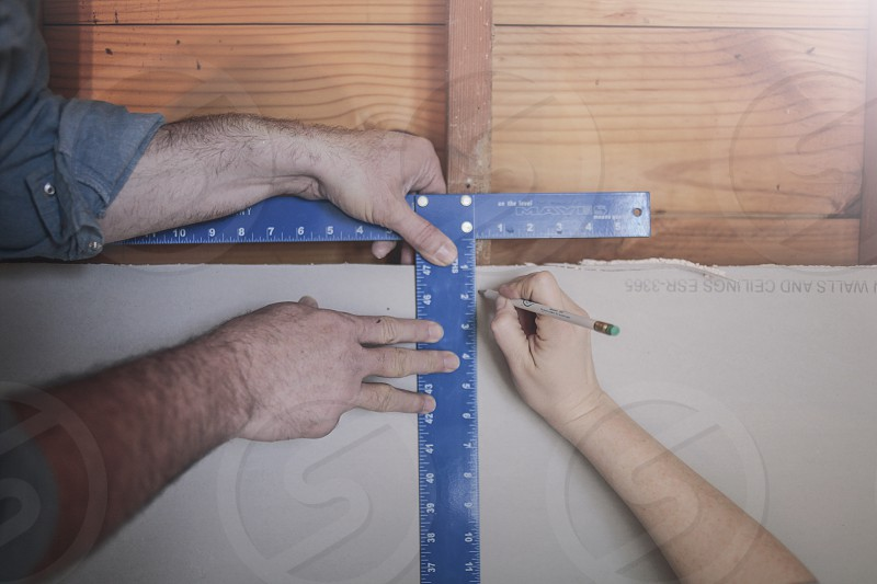 A man and a woman work together on a construction project in their home. This photo focuses on their hands as they measure and mark a wall.  photo