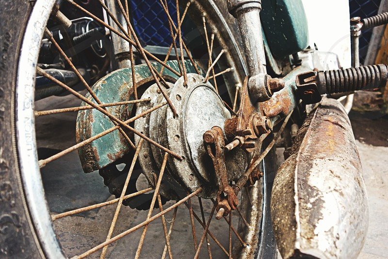 close up rust wheel motorcycle vintage motor chain tire screw spokes old classic photo