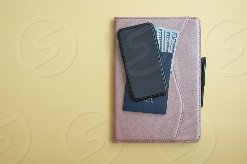 Dollar banknotes passport mobile phone and tablet against the yellow background photo