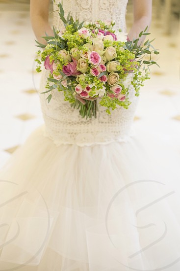 woman in white floral lace gown holding pink and white rose bouquet photo