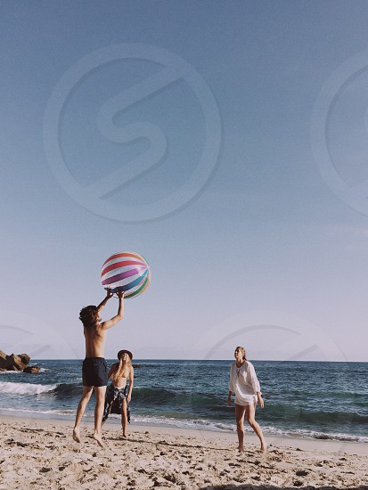 boy wearing black shorts jumping and tossing beach ball to the girl wearing white long sleeved shirt near boy with wrapped dress shirt around his waist at the shore below bright blue sky during daytime photo