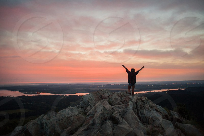 man standing on the top of rock formation photo