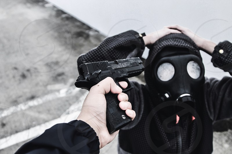 man holding glock pistol pointing to man with gas mask photo