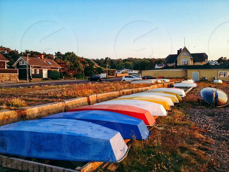 Boats in different colors lying up side down in a row on the shore photo