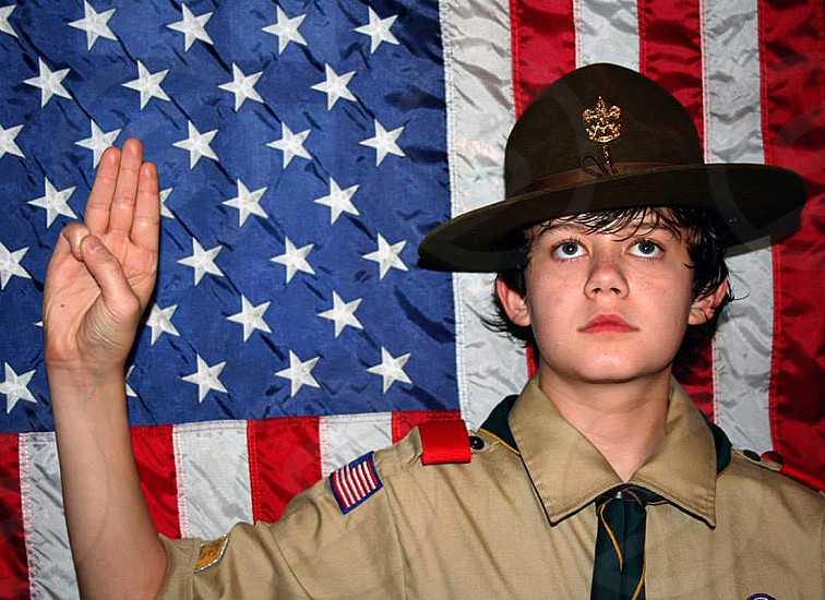 Boy scout pledging his honor in front of American Flag. photo