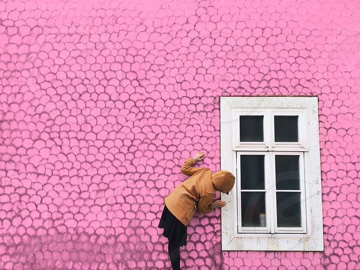 woman in brown hooded jacket and black skirt leaning in to look in a white window on pink house photo