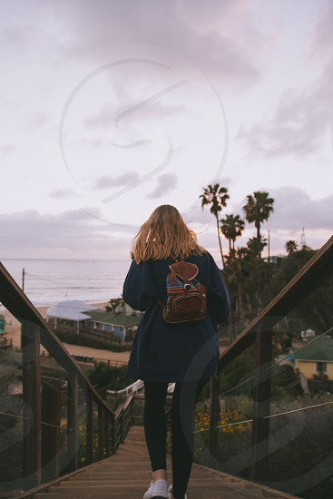 woman in blue jacket and black leggings and white shoes with brown leather backpack walking down on wooden stairs with wooden railings leading to buildings and tall green palm trees near calm sea water under grey clouds photo