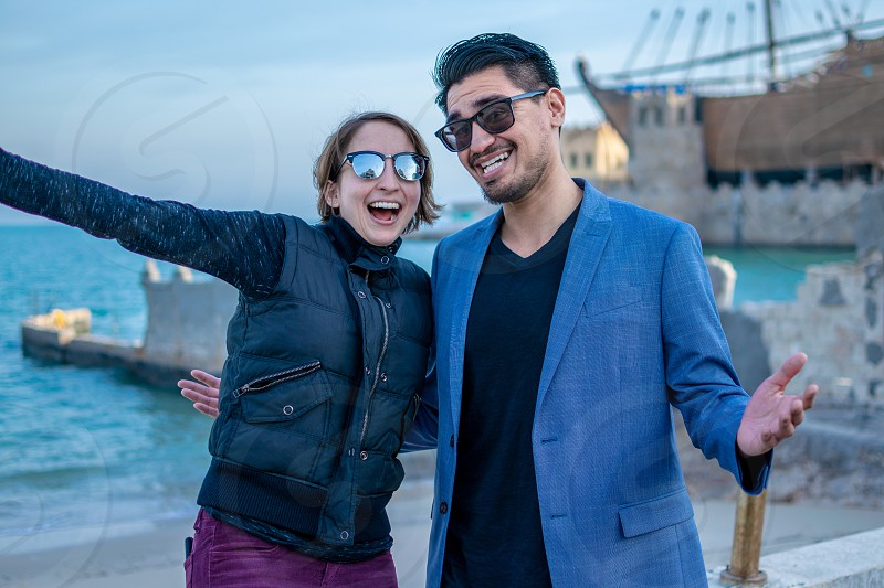 young attractive couple laughing beach in background sunglasses smiling laughter photo