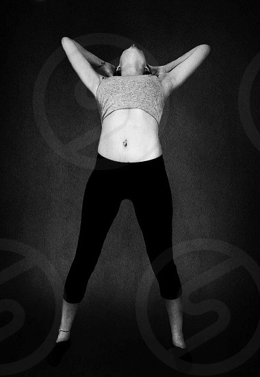 grayscale photo of woman wearing crop top and leggings stretching her body photo