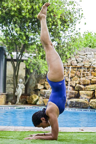 Girl doing yoga by the pool photo
