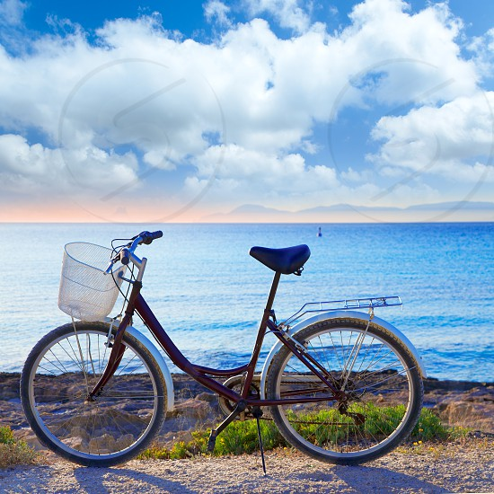 Bicycle in formentera beach on Balearic islands with Ibiza sunset background photo