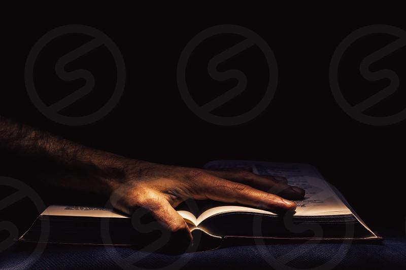 Man's hand on open book studio shot in the dark.  photo
