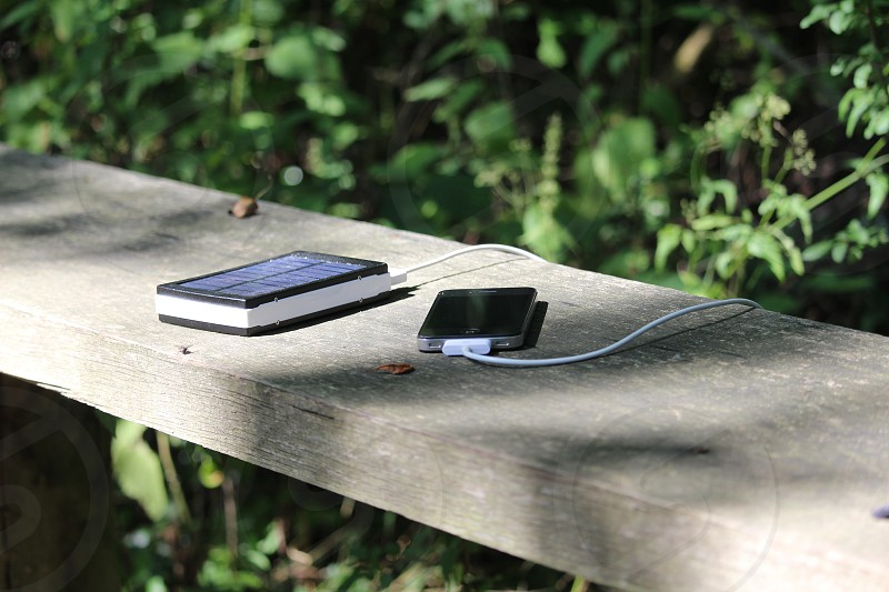 Solar power mobile charging outdoors cell phone bank eco Sun shine sunshine renewable cable iPhone friendly environment electricity charge  photo