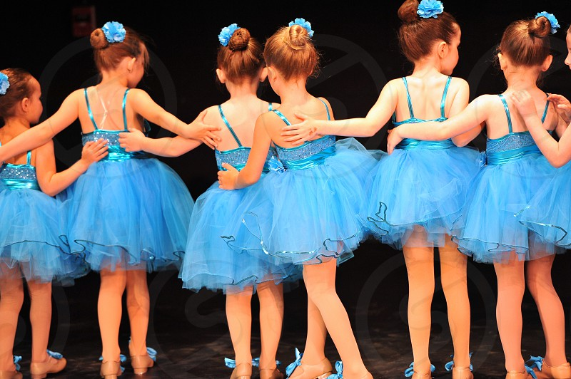 Young female dancers in a row with backs facing. Beautiful blue dresses with bows in shoes and hair. Arms around each other. photo