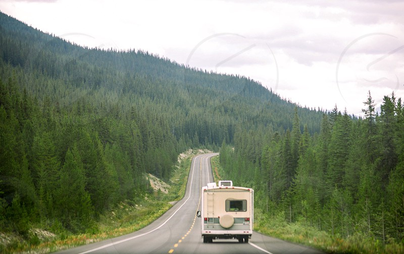 photography of beige RV on empty road photo