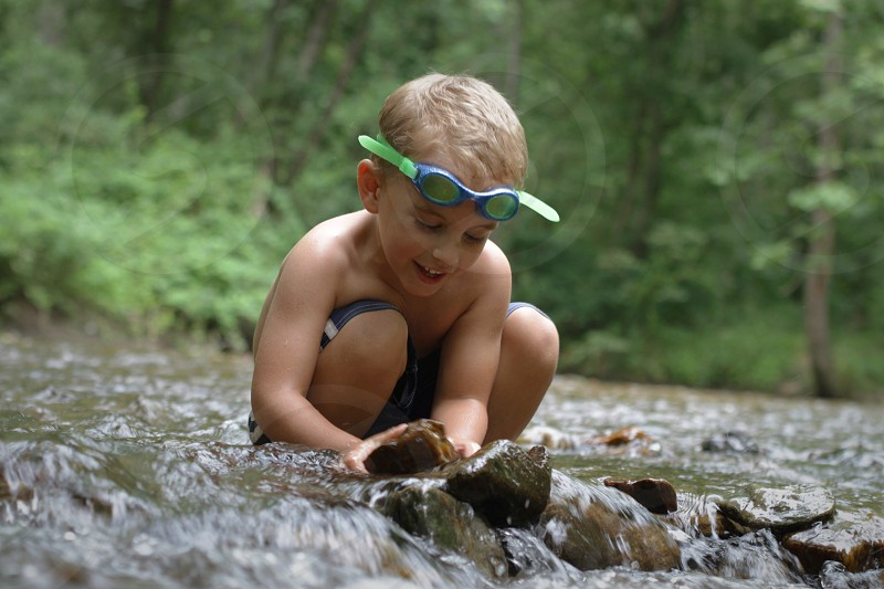 boy sitting holding rock on a river photo