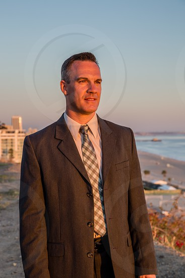 Attractive man in a suit looking off to sunset photo