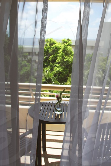 view through gray curtains onto a patio with a round black table photo