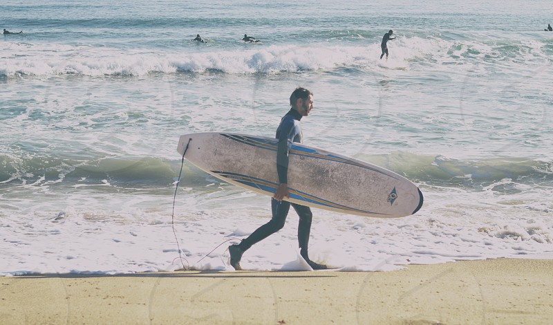 man holding white and blue surfing board walking photo