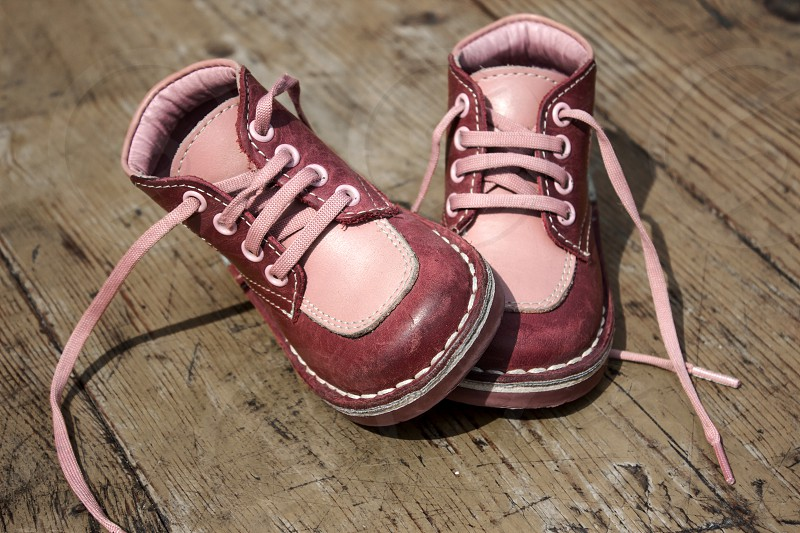 Kid's leather shoes on wooden background photo