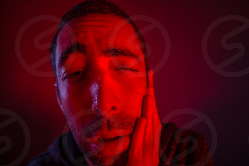 Sweating man having toothache. Close up headshot portrait of man having fever or drugged him or poisoned him. photo
