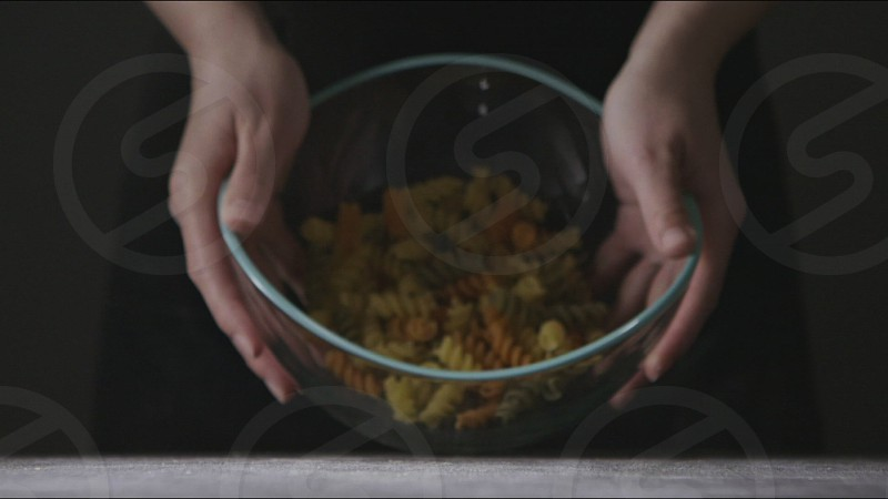 Raw italian pasta Fusilli Spirale colorful pours from glass bowl in a girls's hands on a dark wooden background. Slow motion Full HD video 240fps 1080p. Close up view. photo