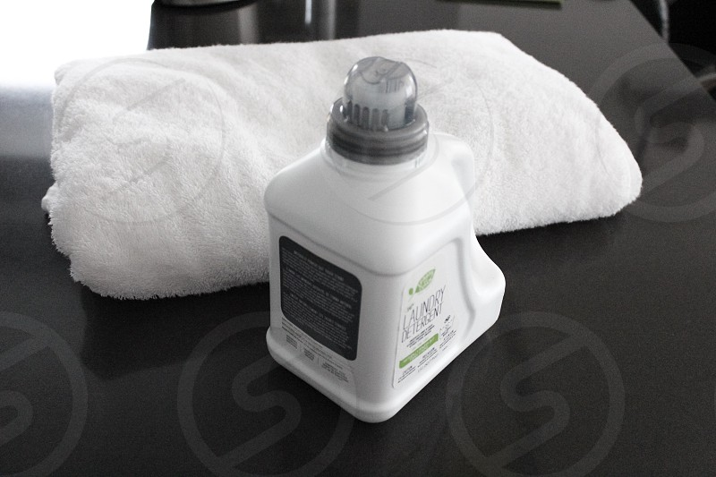 white lotion bottle and white folded towel on a countrtop photo