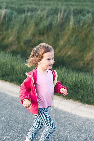 Little adorable girl having fun running on road playing outdoors photo