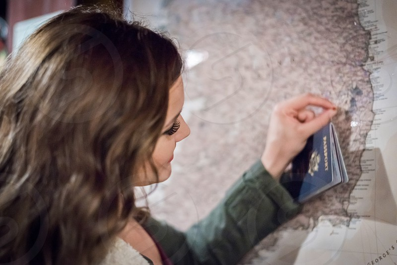 Young woman inserting a push pin into a map. photo