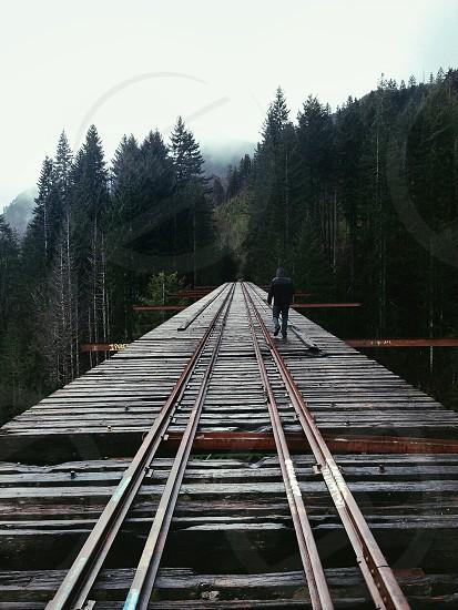 man walking across a wooden bridge photo