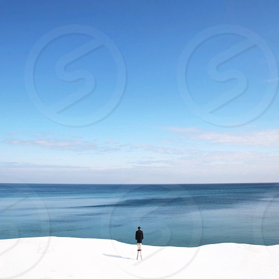 person in black standing on white snow capped mountain with view of ocean at distance photo