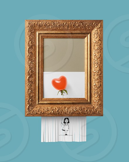 Vintage frame with a selfdestructive picture of a smiling girl holding a balloon made of tomato in the shape of a heart on blue background modern art photo