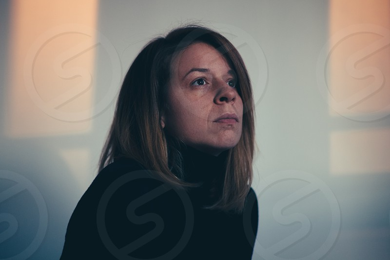 A woman sitting alone and depressed in window light photo