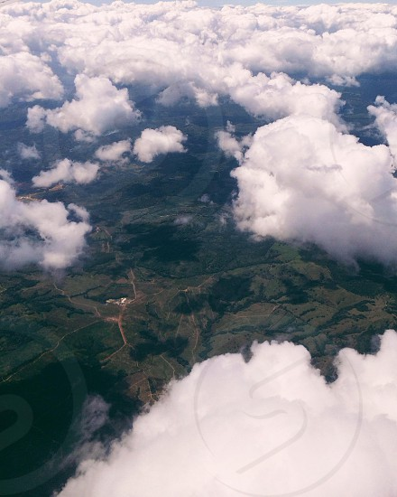 birds-eye view of dark green hills beneath white clouds photo
