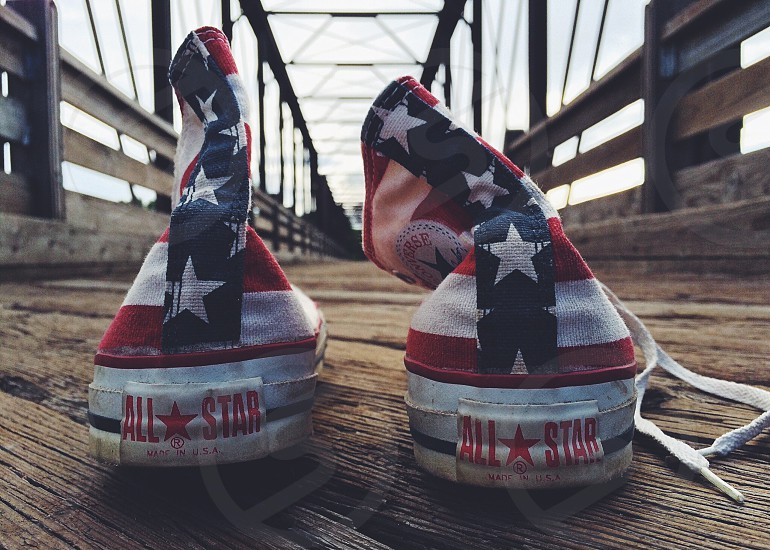 pair of white-red-and-blue Converse All-Star America-themed high-tops on brown wooden pavement photo