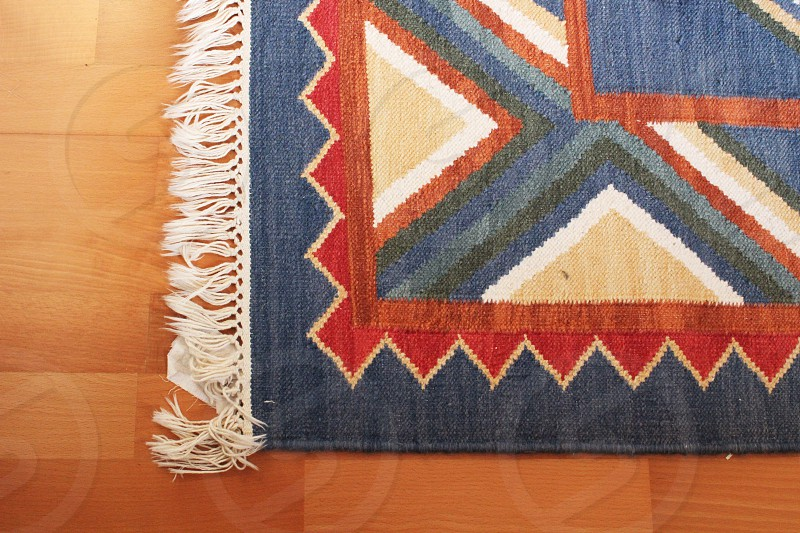 blue red tan woven tribal print area rug with white fringe photo
