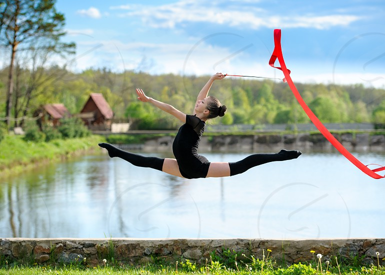 Young gymnast girl doing exercise with red ribbon outdoor. She making leg-split in a jump on background of pond and woods photo